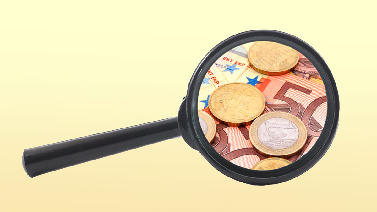 money and magnifying glass showing financial success