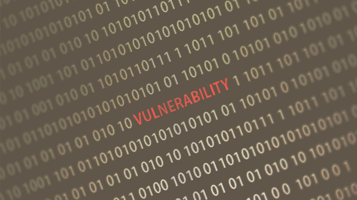 'Vulnerability' word in the middle of the computer screen surrounded by numbers zero and one. Image is taken in a small angle. Image has a vintage effect applied.