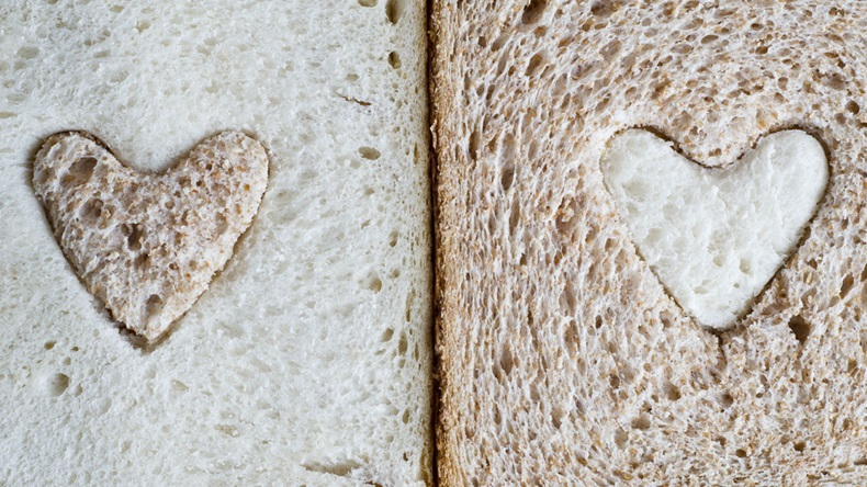 white bread slice with a brown wholemeal heart, and a wholemeal bread slice with a white heart