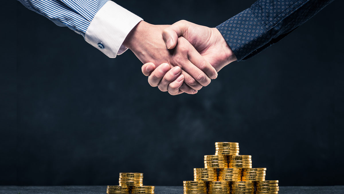 Handshake of businessman over coins