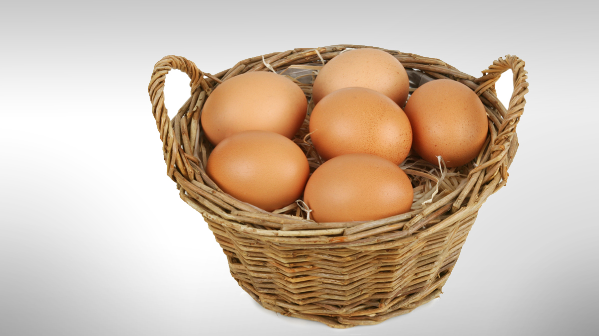 Wicker basket with six brown eggs. Isolated on white. Clipping path included.