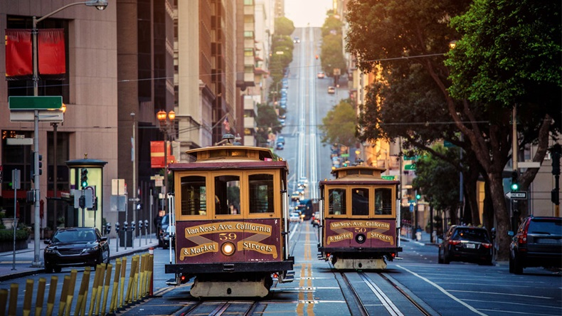 Classic view of historic traditional Cable Cars riding on famous California Street in morning light at sunrise with retro vintage style cross processing filter effect, San Francisco, California, USA - Image