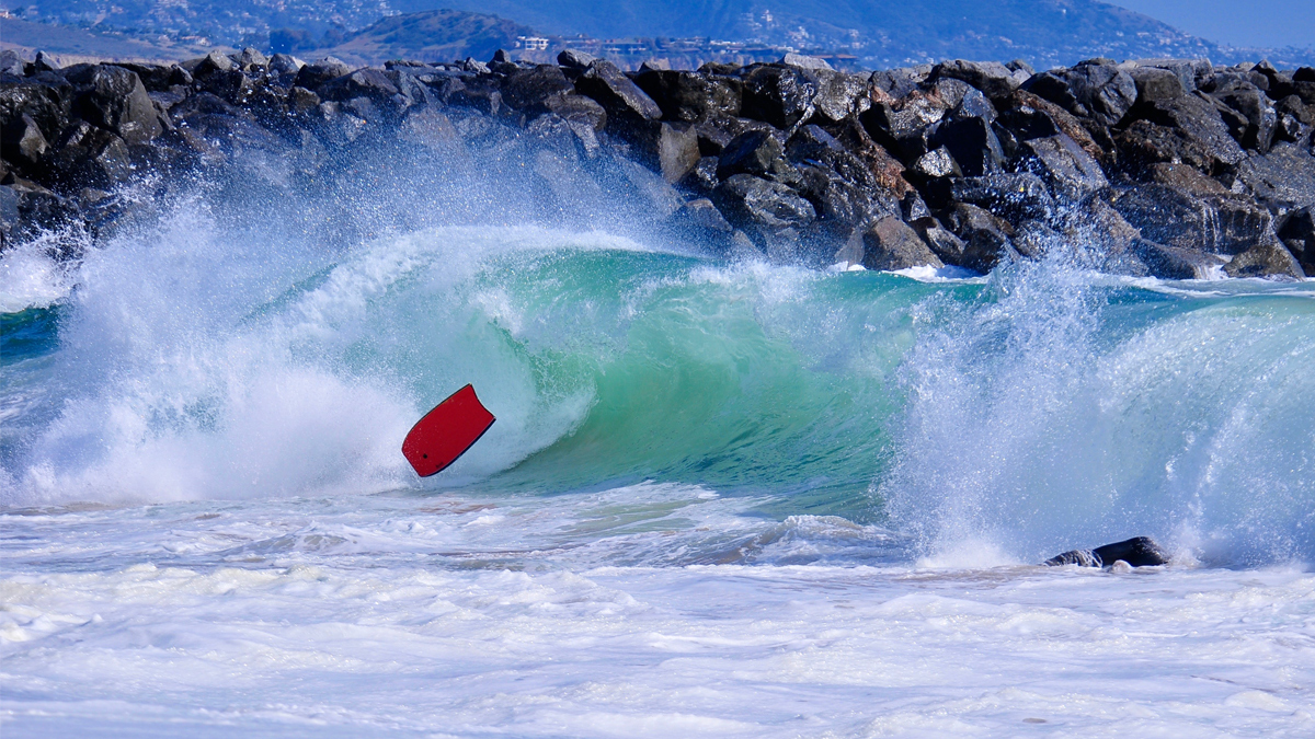 Bright, blue green wave breaks on body boarder and sends red board flying at the Wedge, Newport Beach. - Image