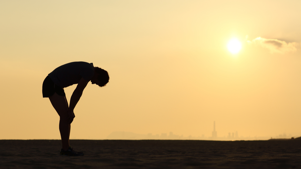 Silhouette of an exhausted sportsman at sunset with the horizon in the background - Image