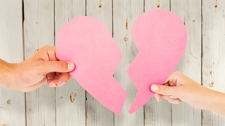 Couple holding two halves of broken heart against wooden background - Image