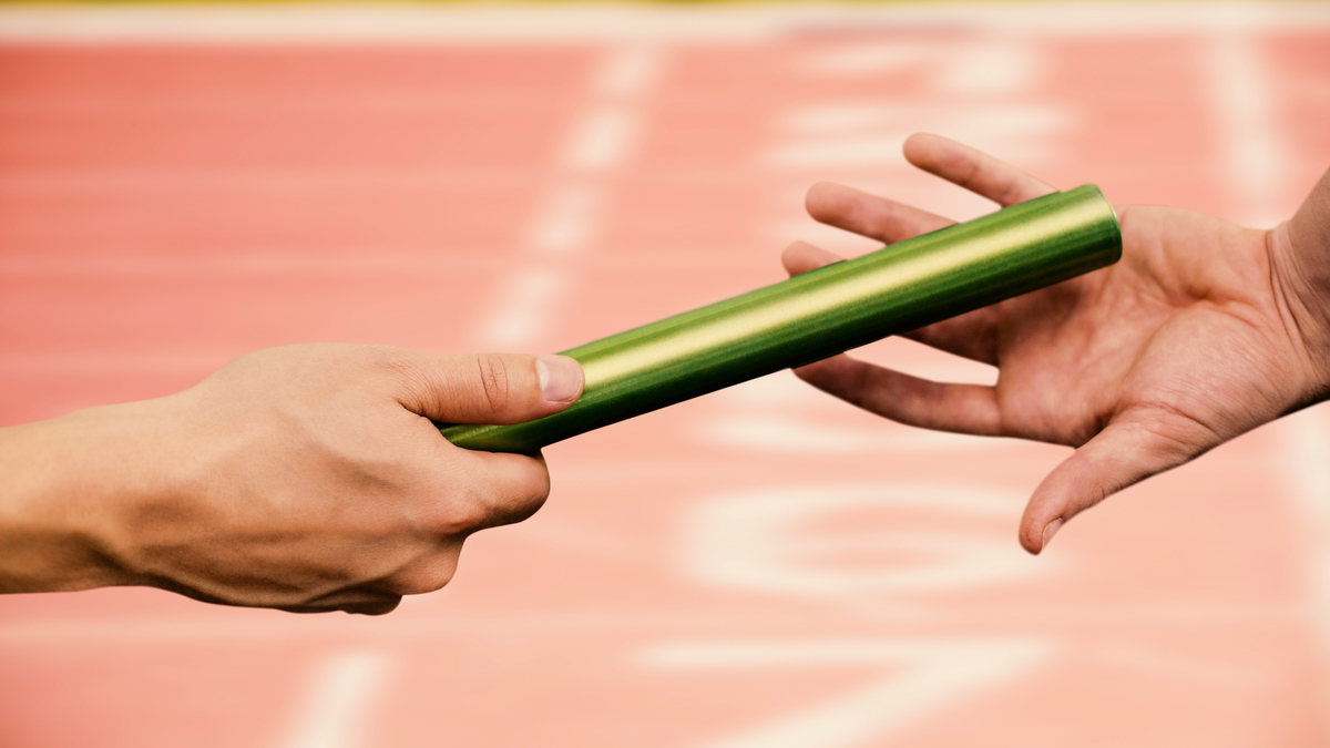 Man passing the baton to partner on track against close up of the track starting point - Image