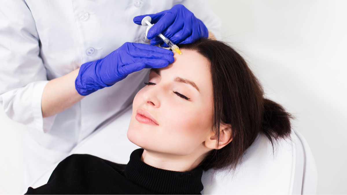 Close up of hands of cosmetologist making botox injection in female face