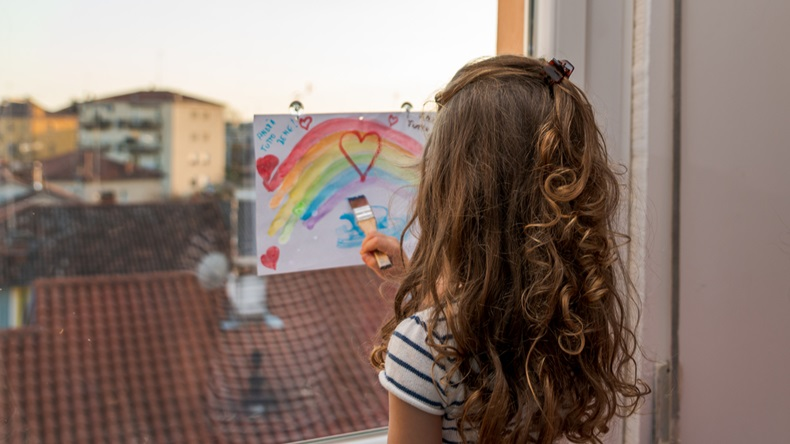 little girl is painting a rainbow to a sheet of paper attached on her window during the covid-19 quarantine in italy