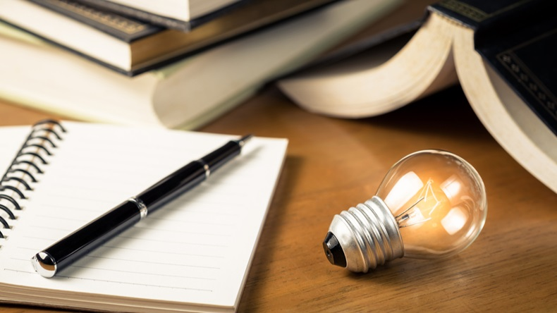 Small light bulb glowing on the desk, with notebook