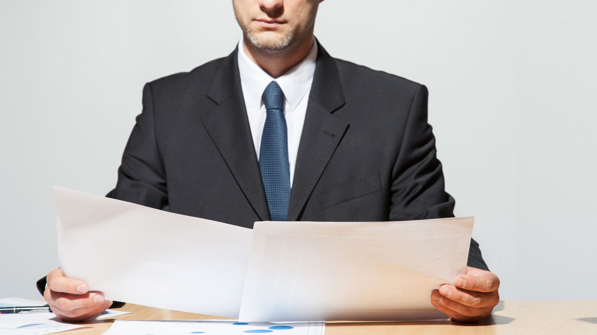 Businessman comparing two documents, neutral background