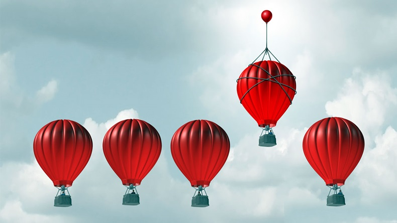 Competitive edge and business advantage concept as a group of hot air balloons racing to the top but an individualleader with a small balloon attached giving the winning competitor an extra boost.