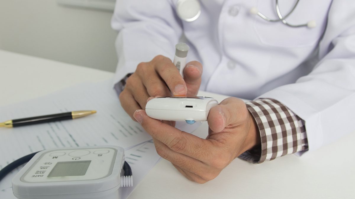Doctor checks blood glucose monitor to meet with diabetic patients.
