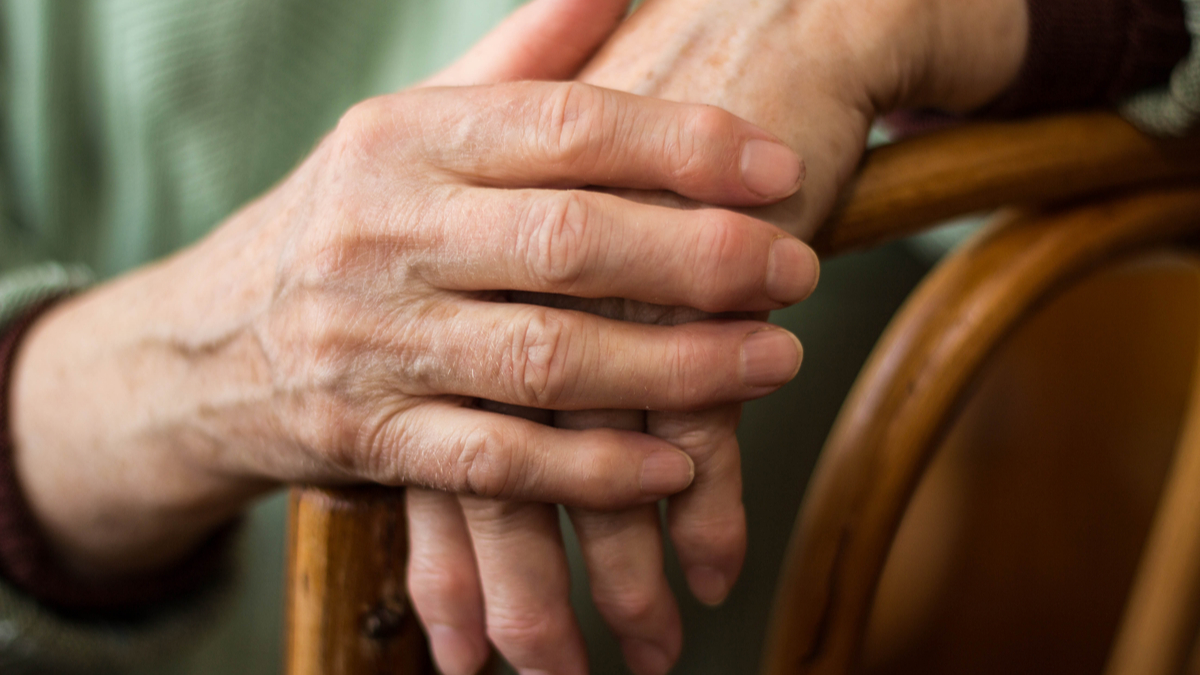 two hands of an elderly woman sitting on a chair - Image