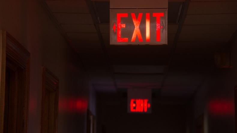 Two lighted glowing red exit signs in an office hallway with arrows pointing the way out of the building.
