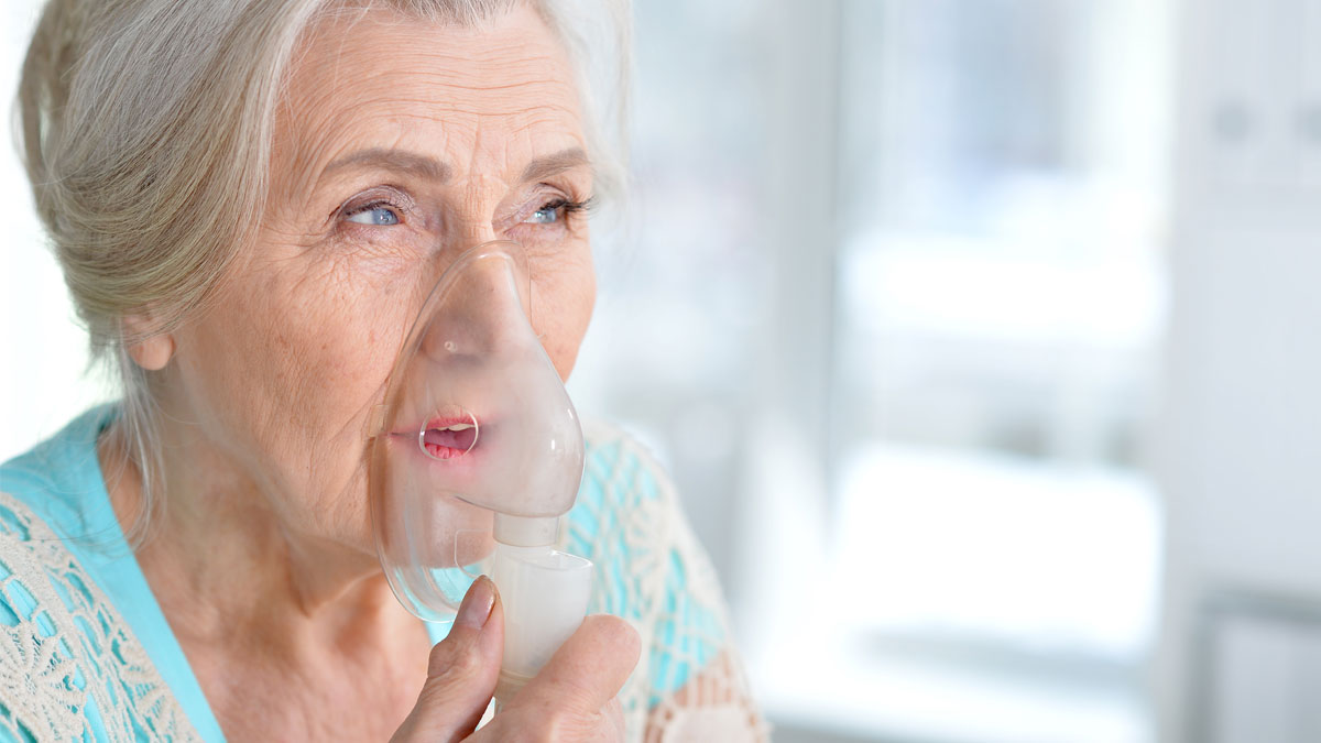 Sick elderly woman making inhalation