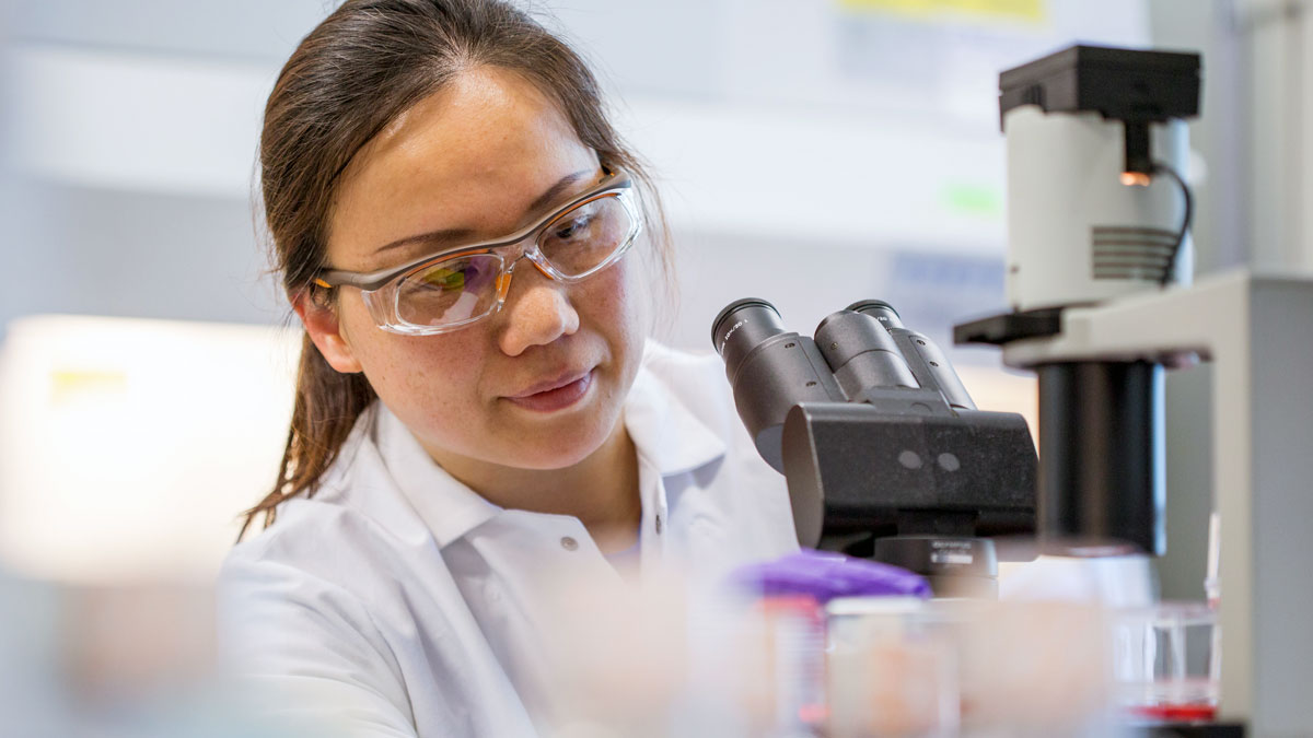 female scientist working with microscope